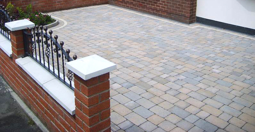 driveway design in london block paving and red brick garden wall with rails