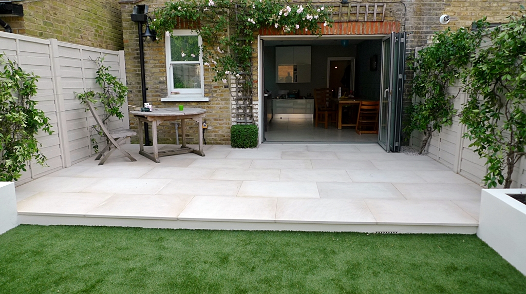beige sawn smooth cut sandstone patio with easy grass lawn clapham london