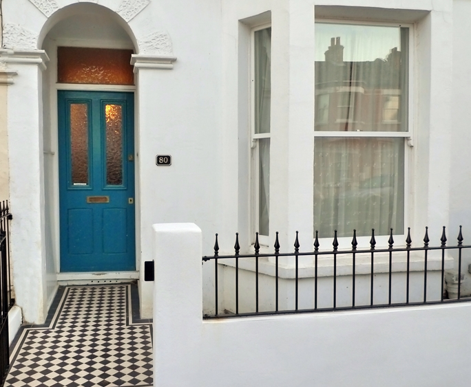 black and white mosaic tile path with white painted wall with metal rail and iron gate london (4)