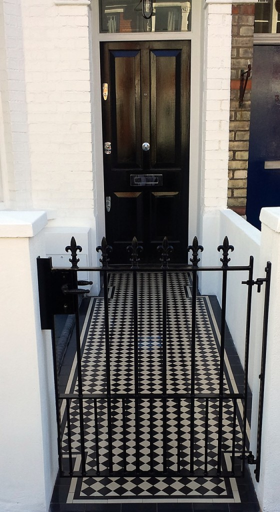 Victorian black and white mosaic tile garden path with rendered walls metal gate london
