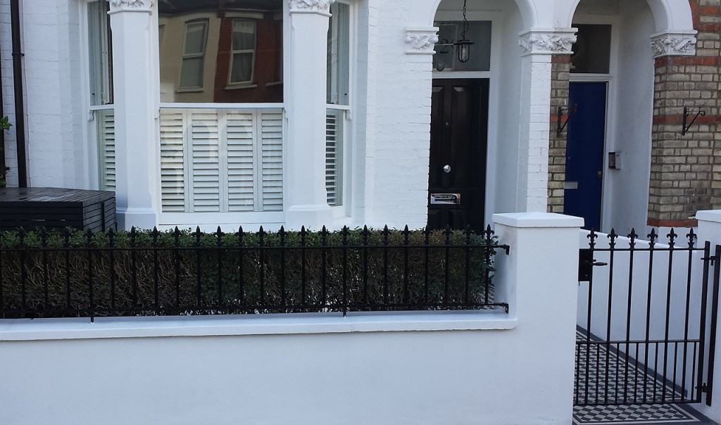 metal wrought iron rail and gate with render plaster wall