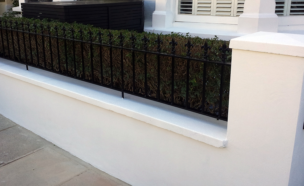 rendered block white painted wall with metal rail