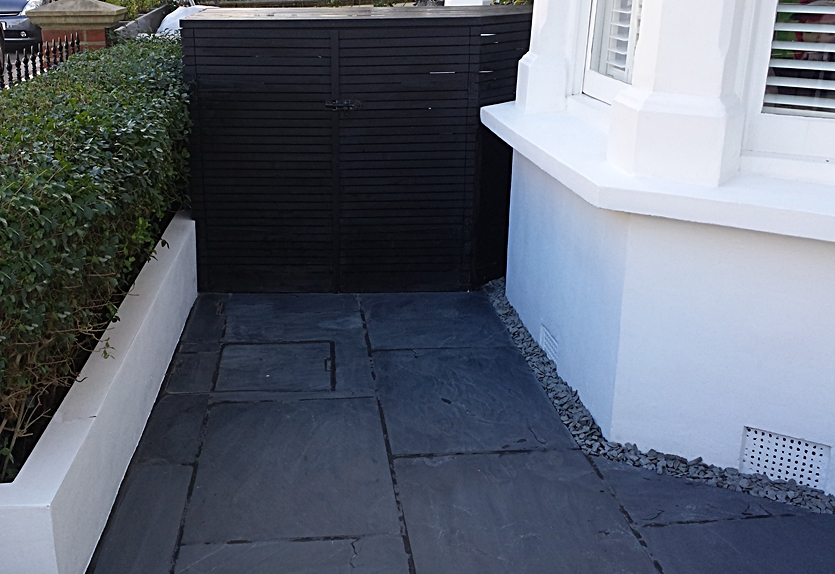 slate paving patio and black slatted bin store