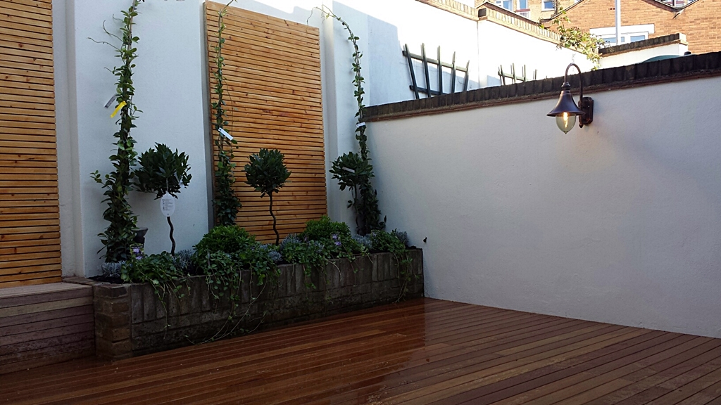hardwood decking formal planting rendered walls slatted screen elegant lighting garden london small