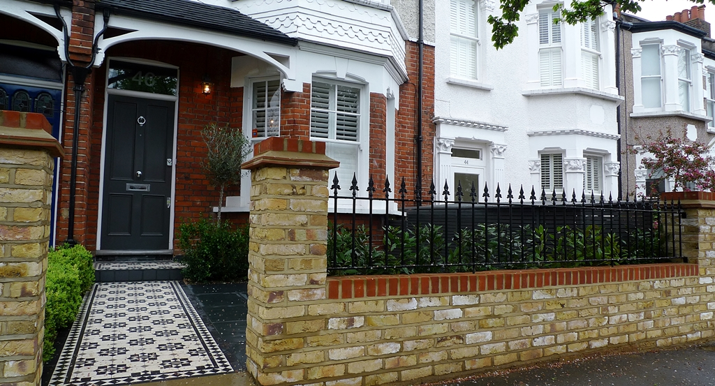 Stock yellow brick london garden wall with metal rail and formal planting hedge wimbledon