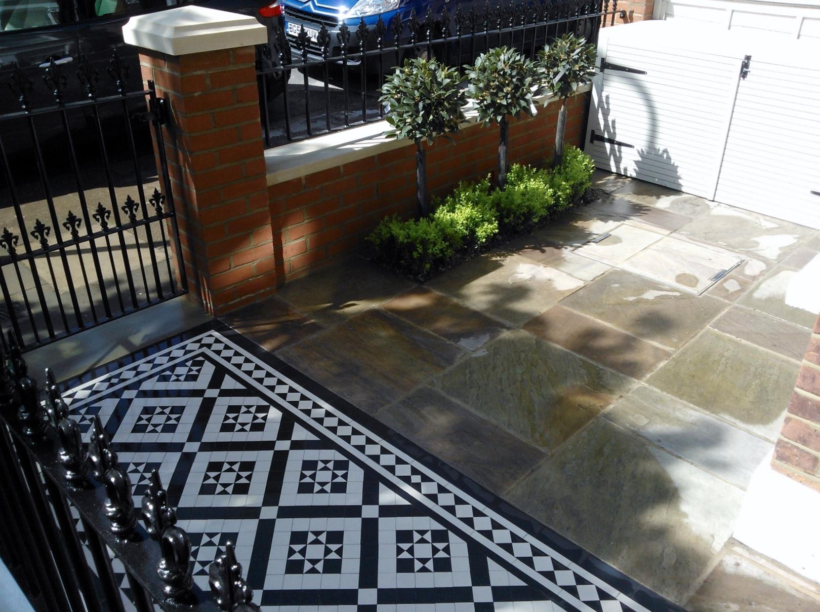 Black and white victorian mosaic tile path red brick garden wall