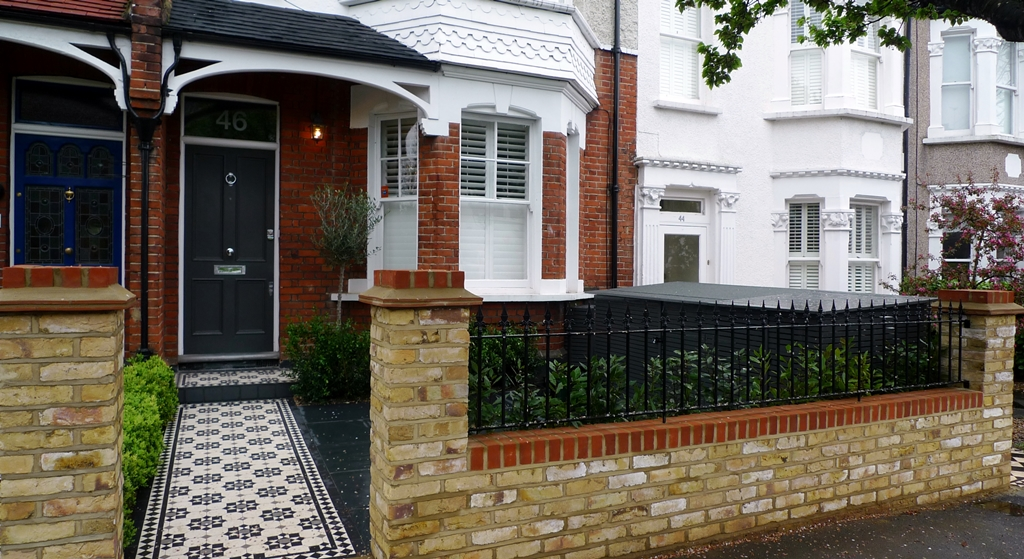 yellow brick london garden wall with metal rail and formal planting hedge