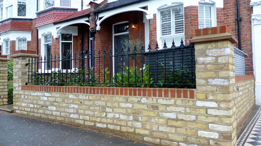 yellow brick london garden wall with metal wrought iron rail and formal planting hedge