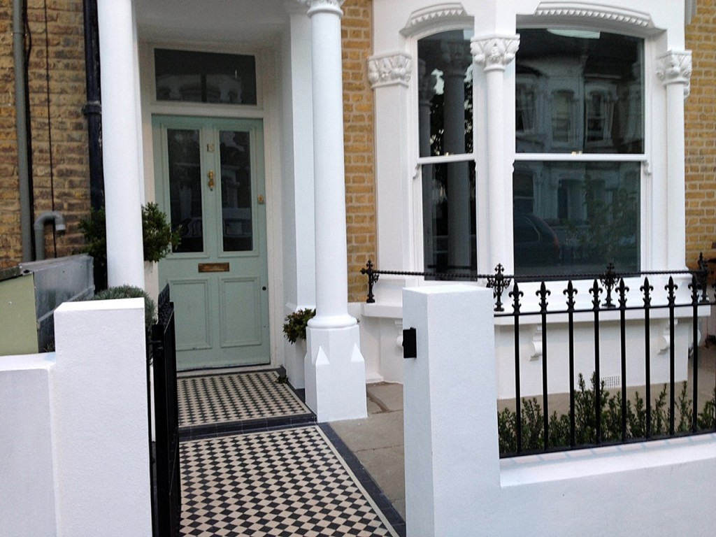 Black and white victorian mosaic tile path rendered plastered white walls with wrought iron metal rails and gate peckham new cross london