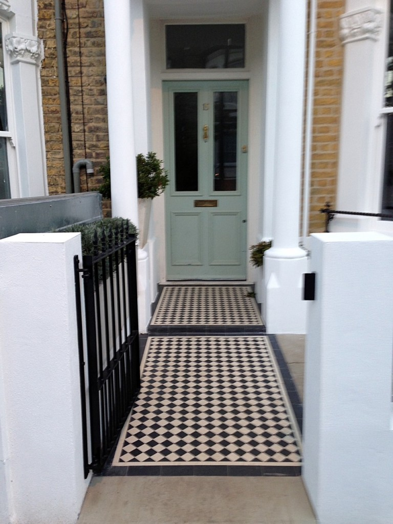 black and white victorian mosaic tile path rendered plastered white walls with wrought iron metal rails and gate peckham new cross london (2)