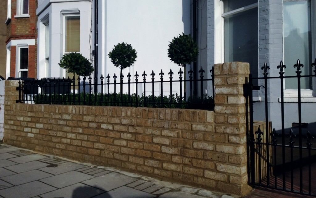 Yellow brick garden wall metal rail and gate bay and buxus topiary Clapham Battersea Balham London (1)