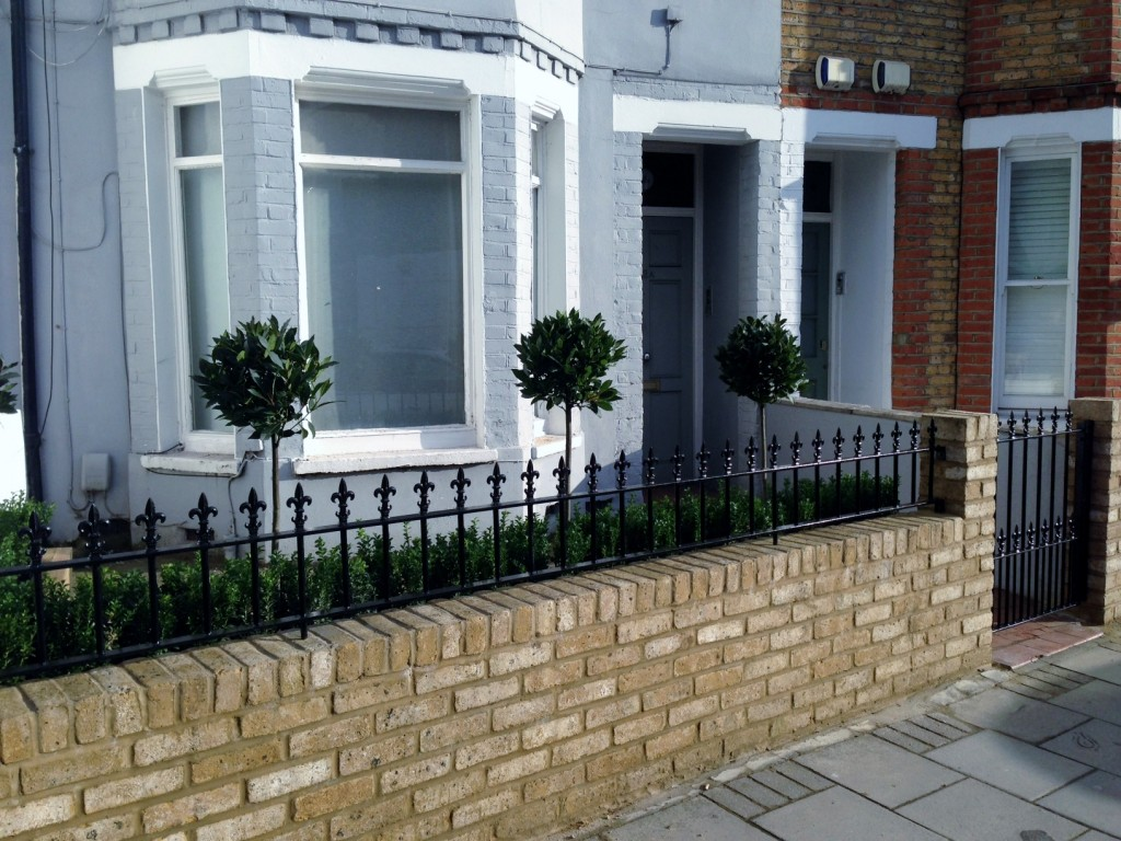 Yellow brick garden wall metal rail and gate bay and buxus topiary Clapham Battersea Balham London (3)