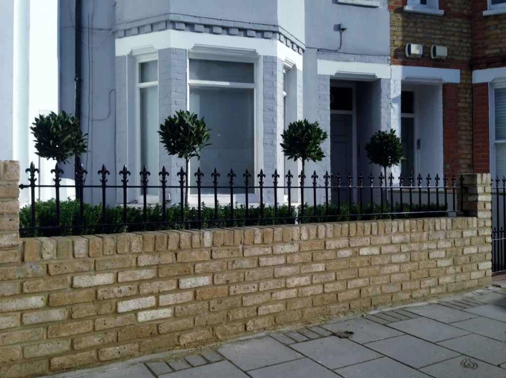Yellow brick garden wall metal rail and gate bay and buxus topiary Clapham Battersea Balham London (7)
