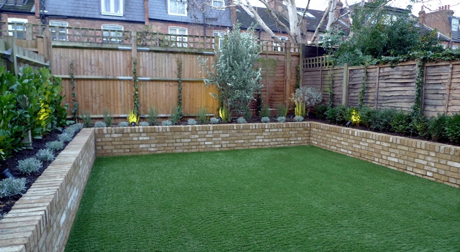Yellow brick raised bed walls artificial fake easy grass for Designs for brick garden walls