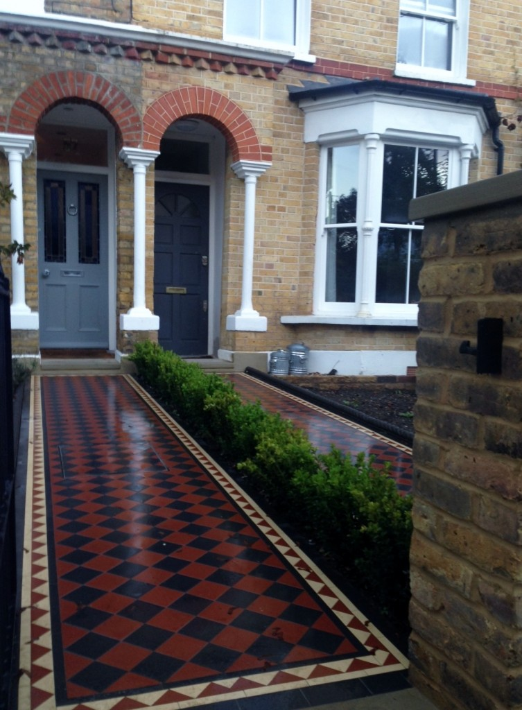 black and red victroian mosaic tile path with meatl gates and yellow stock walls
