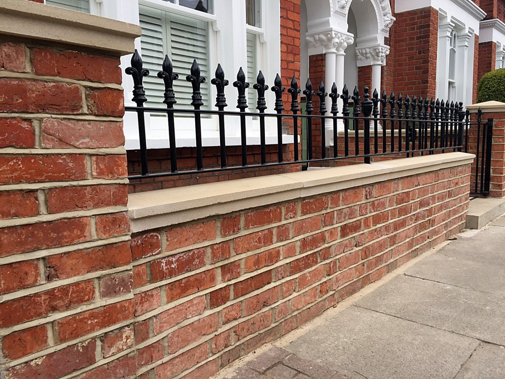 red brick london wall with stone effect caps and solid metal rail clapham