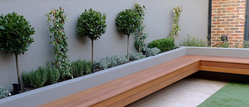 Raised beds artificial grass hardwood strip travertine paving London Battersea Clapham garden deign