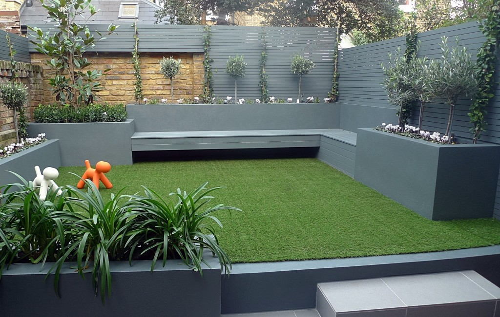 Raised beds grey colour scheme olives agapanthus artificial grass porcelain grey tiles yellow stock brick walls grey Floating bench Balham Clapham Wandsworth