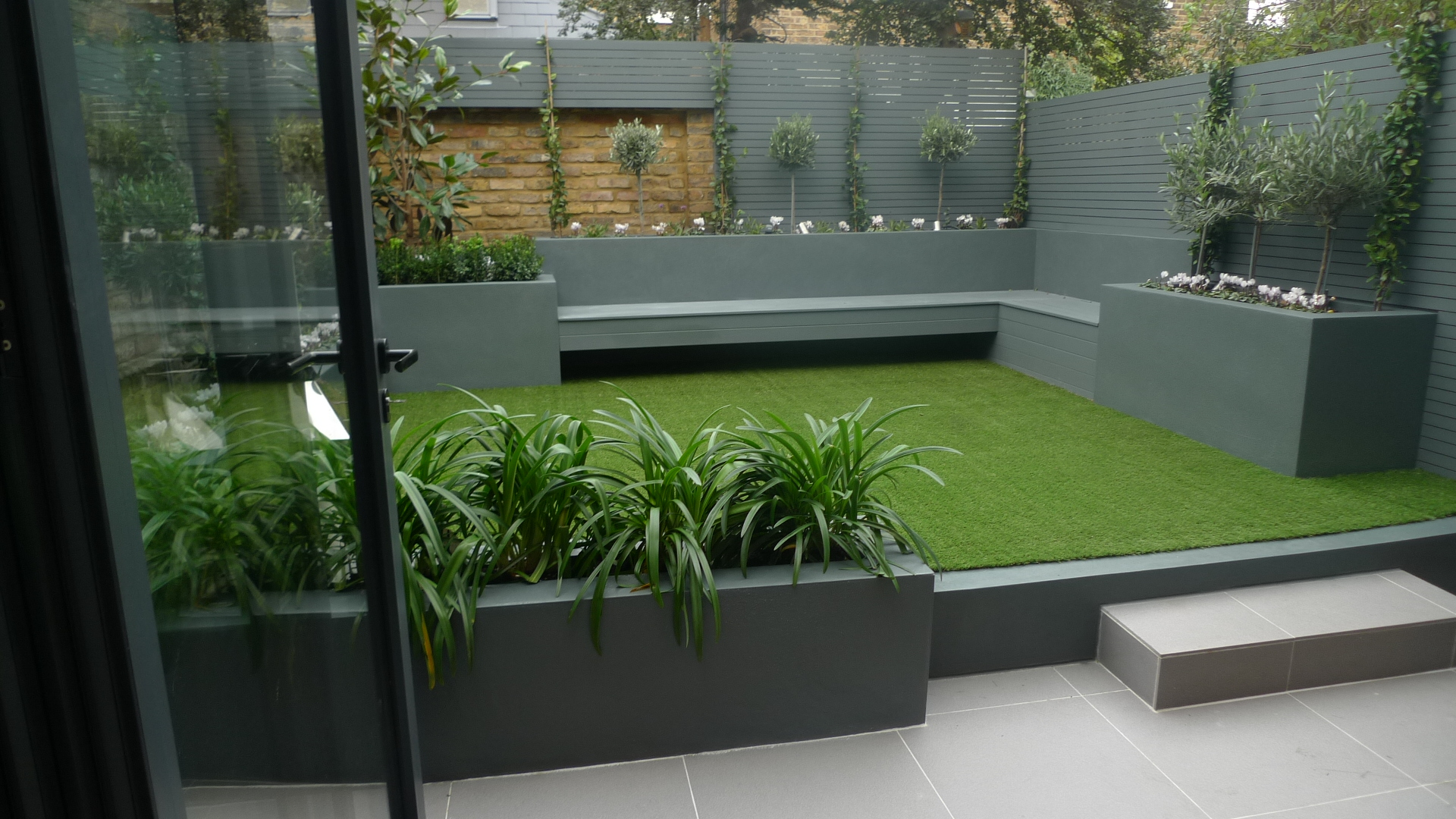Modern small low maintenance garden fake grass grey raised for Photo de jardin moderne