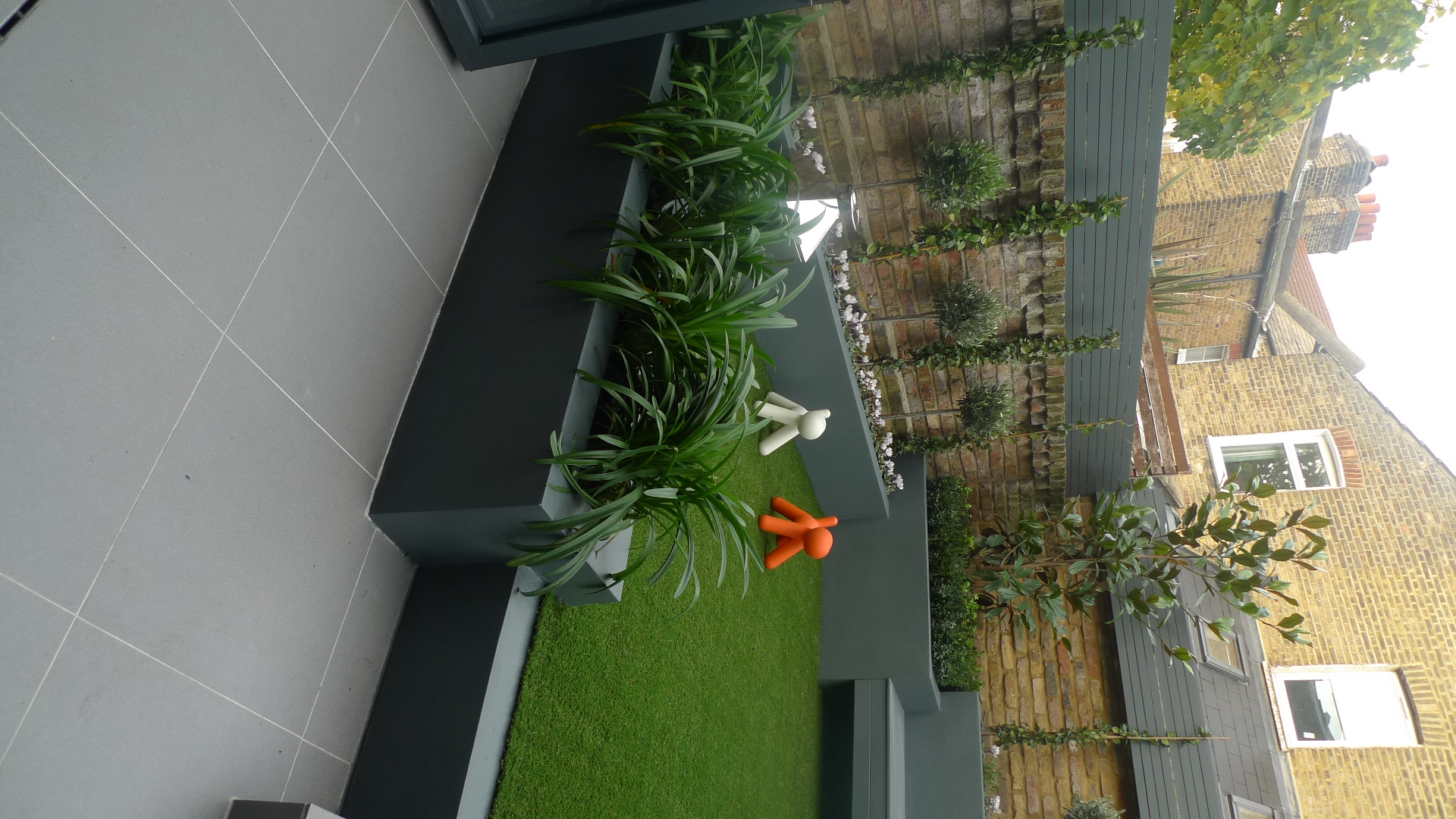 modern small low maintenance garden fake grass grey raised beds contemporary planting battersea