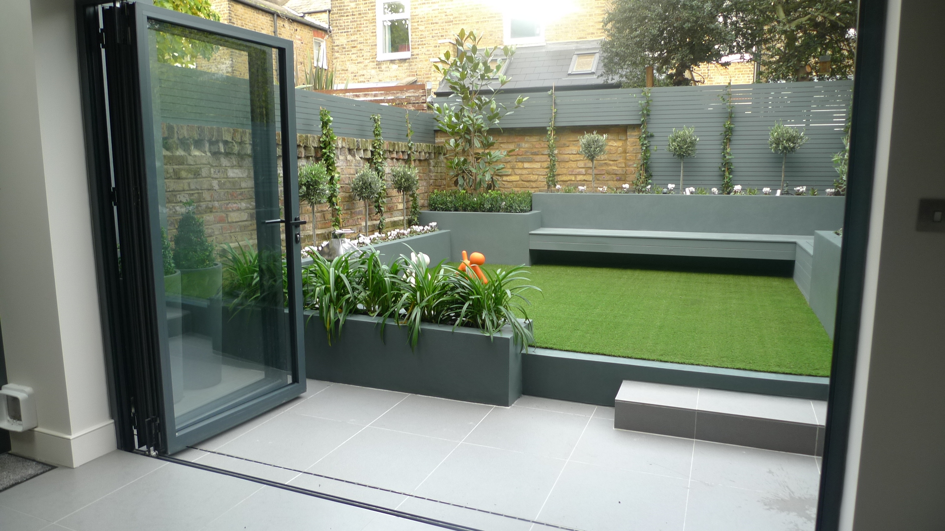 Modern small low maintenance garden fake grass grey raised ...
