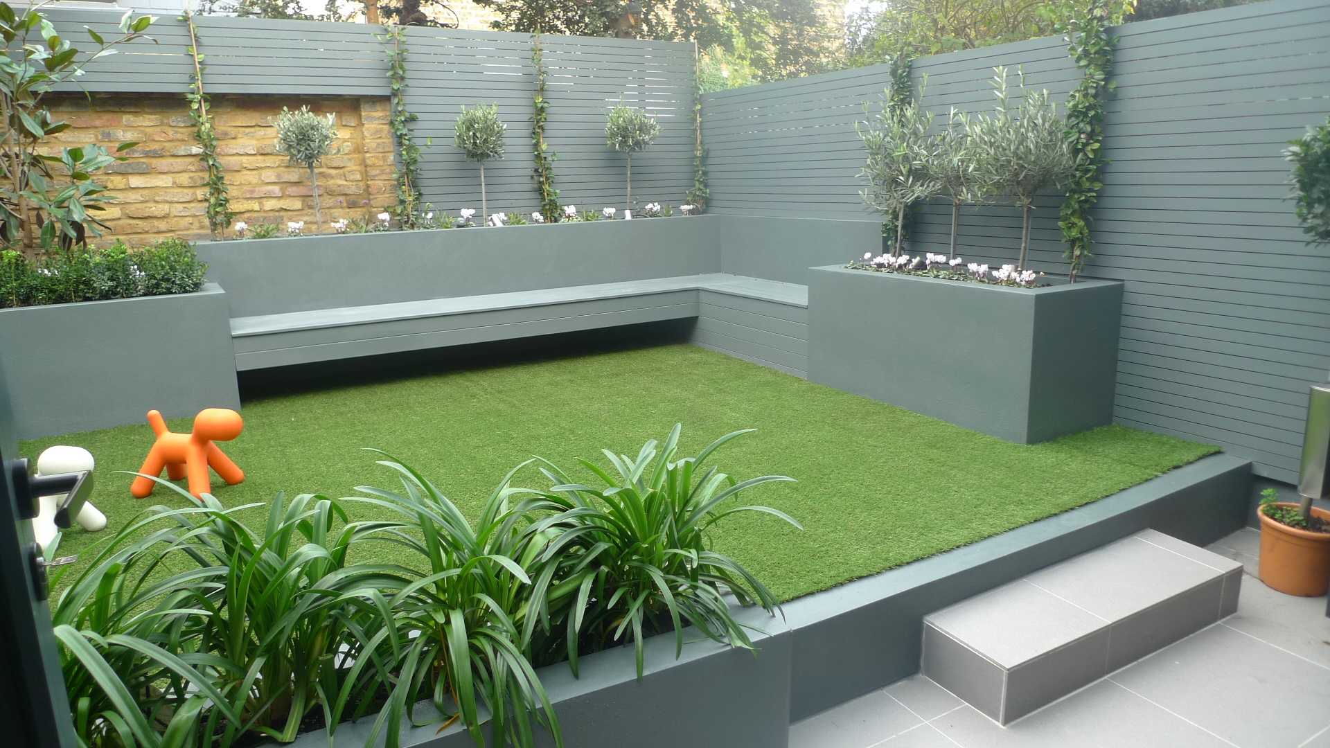 modern small low maintenance garden fake grass grey raised