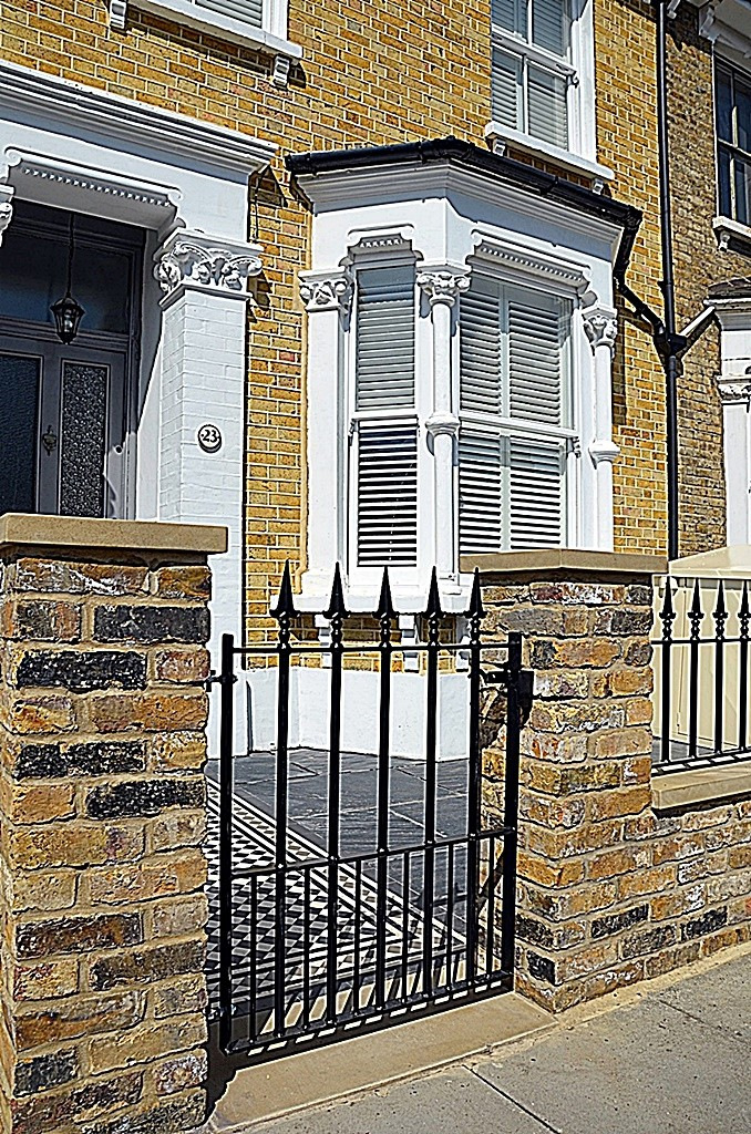 Low maintenance brick garden wall Yellow stock Imperial iron gate rails York stone cap coping piers London